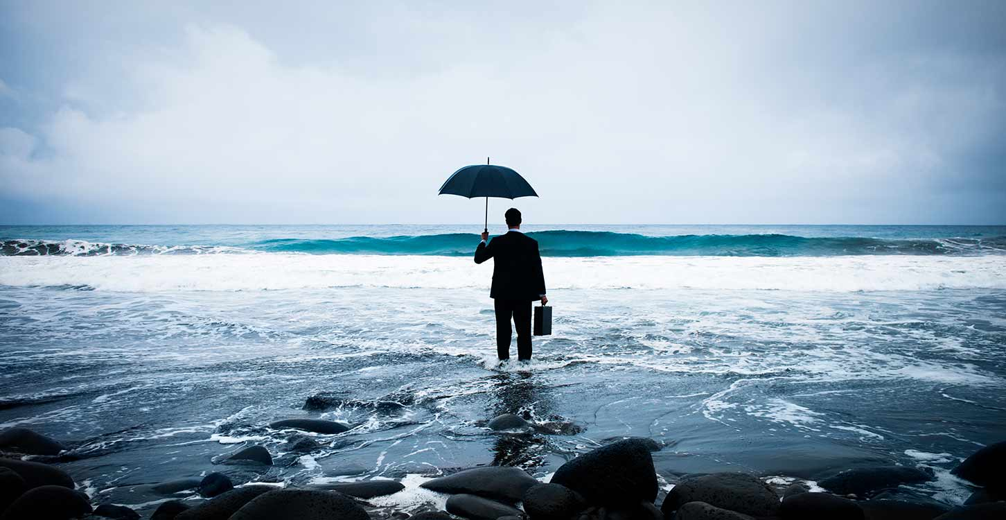 Businessman standing with an umbrella in the ocean